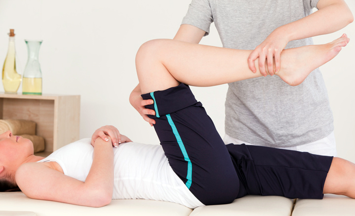 Masseuse stretching the right leg of an athletic woman
